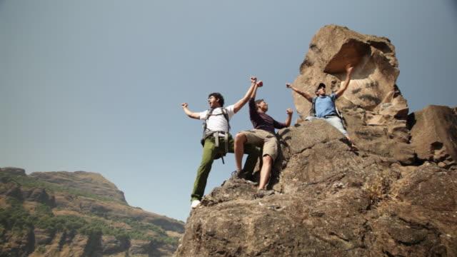 vídeos y material grabado en eventos de stock de three rock climbers celebrating success  - gritar