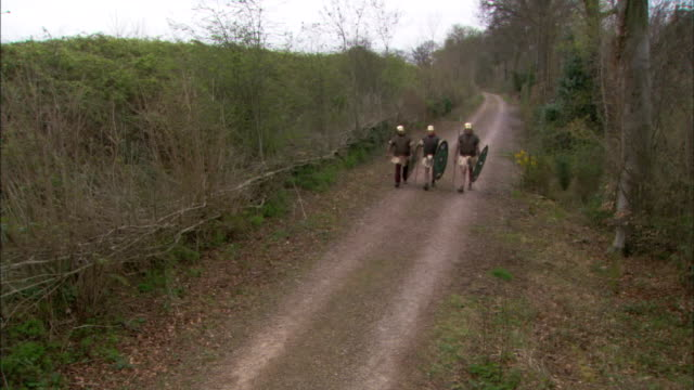 Three Roman soldiers travel along a country trail.