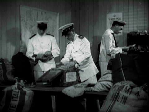 Three Royal British Navy officers sorting through confiscated mail and shipments bound from Germany and Italy one officer opening metal box removes...