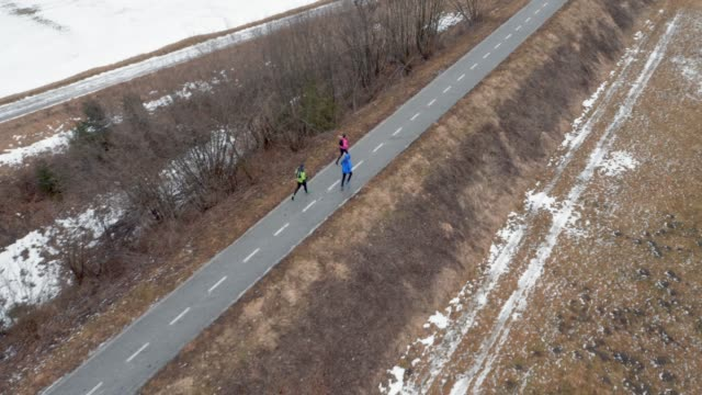 AERIAL Three runners running on a path on a cold winter day