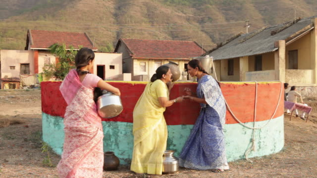 Three rural women filling water from well
