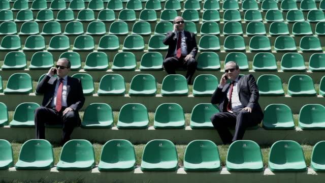 """vídeos de stock e filmes b-roll de três mesmo empresário falando no telefone móvel, sentado sobre o estádio """"bleachers - assento"""