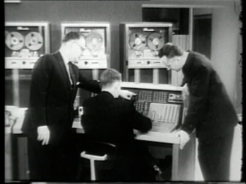 three scholars gathering around computer / scholar punching data in computer keypad / computer tape wheels turning / - punch card stock videos & royalty-free footage