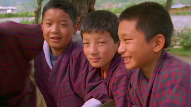 three schoolboys joined by friends as they pose for camera in thimphu available in hd. - bhutan stock videos & royalty-free footage