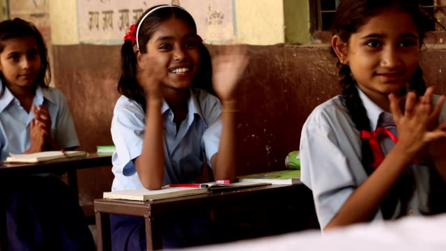 Three schoolgirls clapping in classroom, Haryana, India