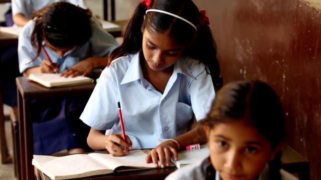 Three schoolgirls studying in classroom, Haryana, India