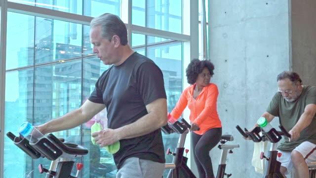 3人の高齢者がエクササイズバイクに乗る - インドアサイクリング点の映像素材/bロール