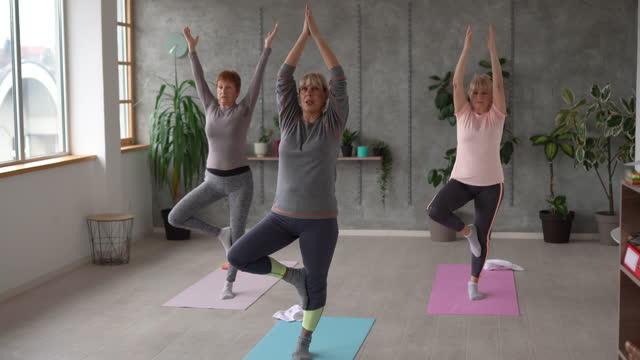 vídeos y material grabado en eventos de stock de tres amigas mayores practicando yoga en el estudio de yoga - vriksha asana