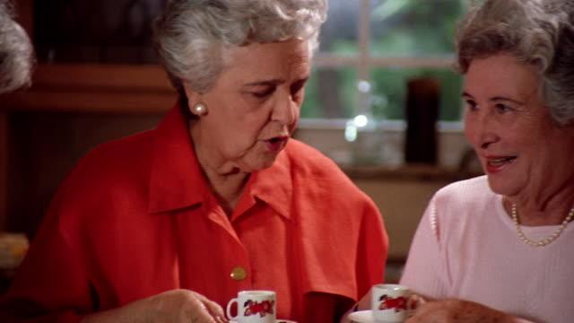 ms pan three senior hispanic women passing cups of coffee in kitchen - only senior women stock videos & royalty-free footage