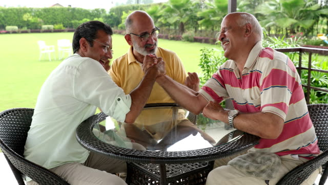 three senior men playing arm wrestling at home, delhi, india - arm wrestling stock videos & royalty-free footage