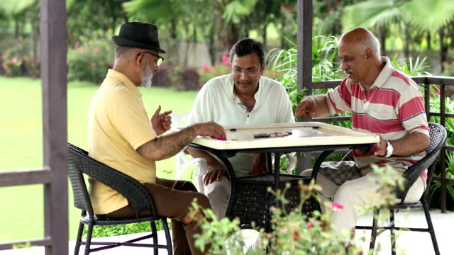 three senior men playing carrom at home, delhi, india - carrom stock videos & royalty-free footage
