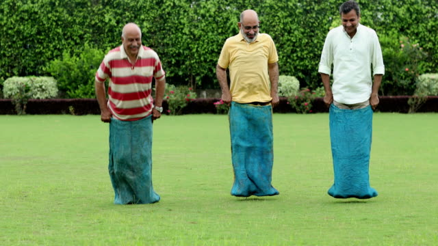 three senior men playing sack race, delhi, india - sack race stock videos & royalty-free footage