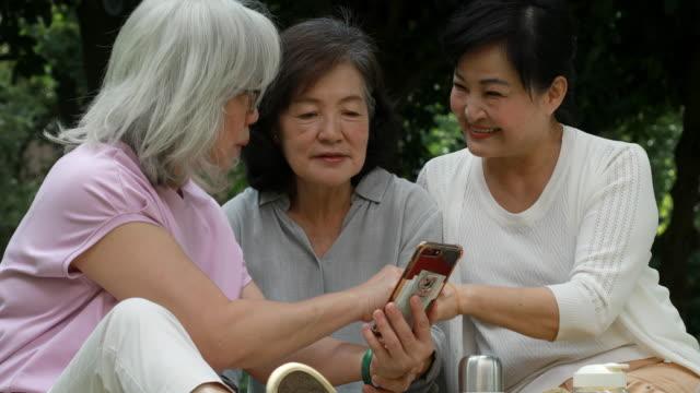 tre senior taiwanesiska damer tittar på smartphone - visning bildbanksvideor och videomaterial från bakom kulisserna