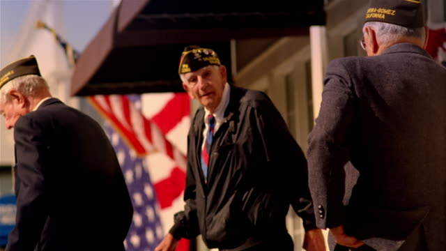 three senior war veterans walking on sidewalk with american flags hanging in background / california - veteran stock-videos und b-roll-filmmaterial