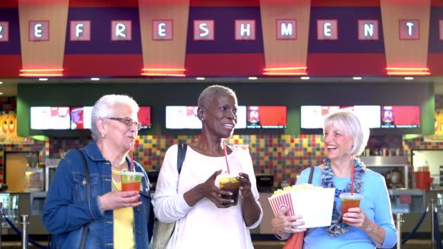 stockvideo's en b-roll-footage met drie senior vrouwen op film theater concessie staan - 70 79 jaar