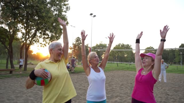 three senior women celebrating after a score while playing a beach volleyball on sand - volleyball sport stock videos & royalty-free footage