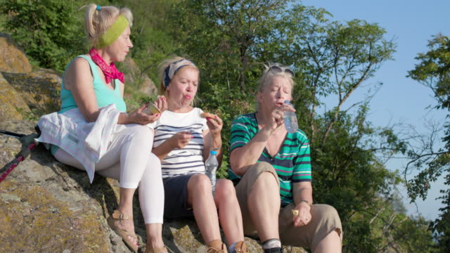 three senior women hikers sitting and eating packed lunch - packed lunch stock videos and b-roll footage