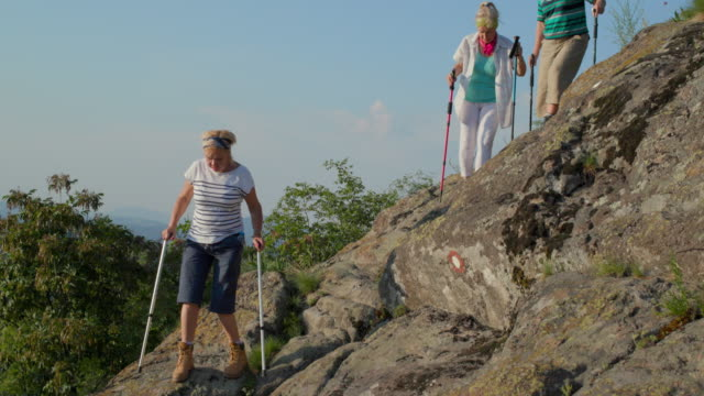 three senior women hiking down rocky hill helping each other - steep stock videos & royalty-free footage