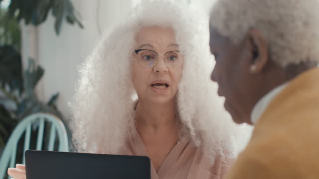 three senior women meeting at home, working at table with laptop and paper - assertiveness stock videos & royalty-free footage