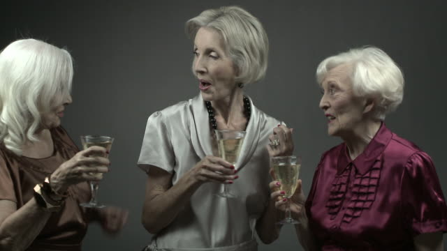 vidéos et rushes de three senior women talking and holding glasses of champagne - millionnaire
