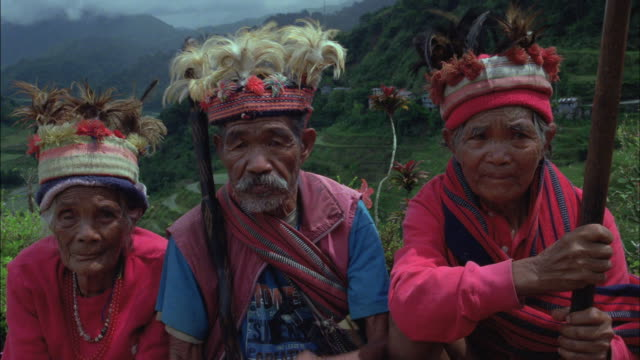 three seniors in traditional dress and head wear sit together as a man plays a mouth harp. - filippine video stock e b–roll