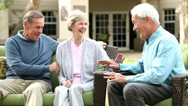 Three seniors sitting on patio talking and laughing