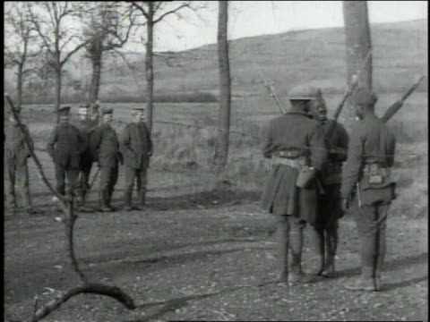 Three sentries with rifles over shoulders talking as Germans stand and watch /