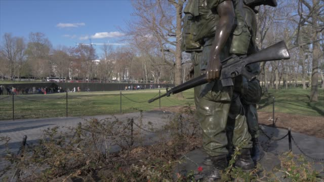 three servicemen statue and vietnam veterans memorial visible in background, washington dc, united states of america, north america - monument stock videos & royalty-free footage