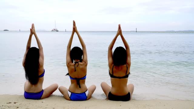 Three sexy woman on a beach practise yoga in bikini