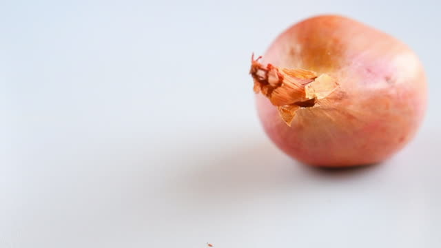 three shallots (onion) moving in slow motion over a white surface - shallot stock videos & royalty-free footage