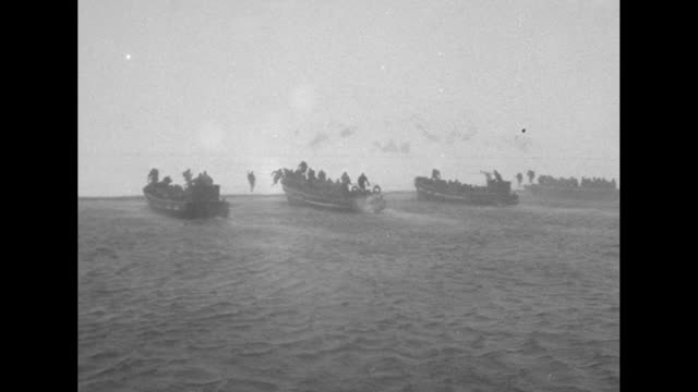 three shots from moving boat of landing barges reaching shore of island of attu and soldiers advancing across beach covered with snow - aleutian islands stock videos and b-roll footage