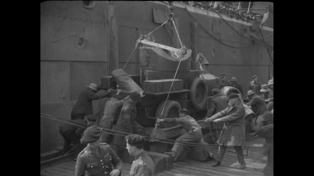 Three shots of a Lanchester Armored Car being hoisted from a cargo ship and British soldiers strain to get it into place / a view of the crowded dock...