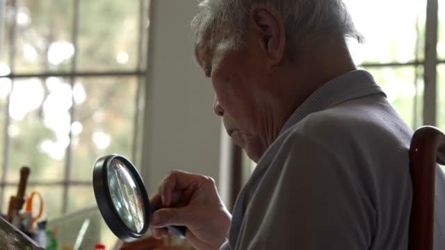 tre bilder av asiatiska senior man med förstorings glas - nyfikenhet bildbanksvideor och videomaterial från bakom kulisserna