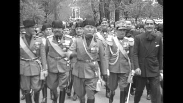 three shots of benito mussolini and officers and blackshirts walking down avenue towards camera / note: exact year not known - benito mussolini stock videos & royalty-free footage