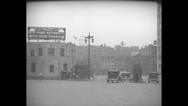 three shots of cars stopping at booth sign on nearby building saying the port of new york authority holland tunnel / note exact year not known - port authority stock videos & royalty-free footage