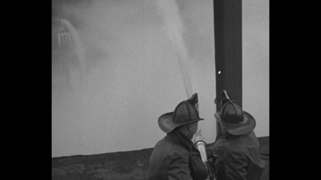three shots of firemen on pier using water cannons to shoot streams of water on burning ship ss muenchen / shot from pier of burning ship and gangway... - kanone stock-videos und b-roll-filmmaterial