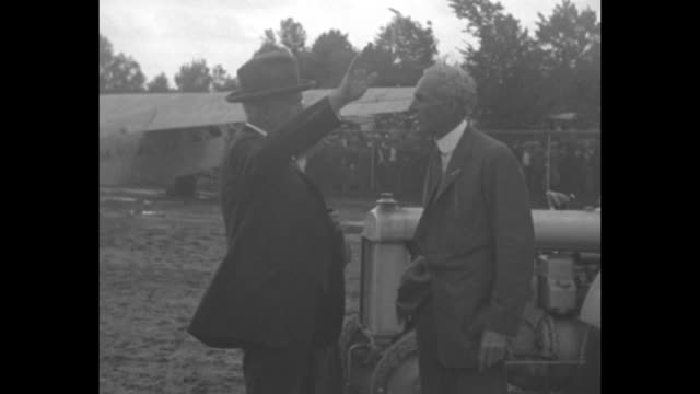 vidéos et rushes de three shots of industrialist henry ford talking with senator james j couzens in front of airplane / line of men standing next to plane man waves flag... - essai de voiture