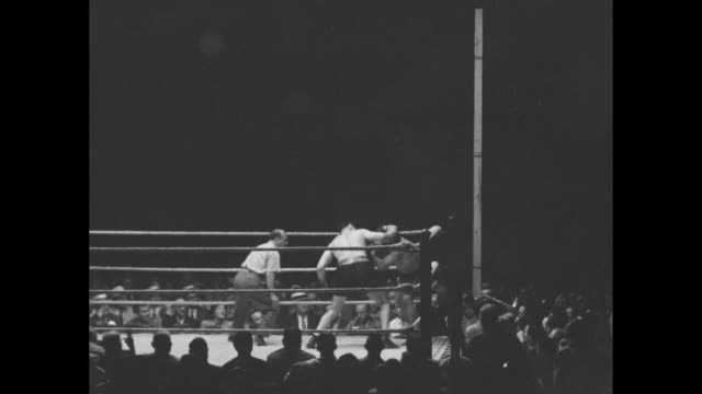 """three shots of jack dempsey pounding wrestler clarence """"cowboy"""" luttrell in corner of ring / man in audience standing and applauding / dempsey lands... - pesi massimi video stock e b–roll"""