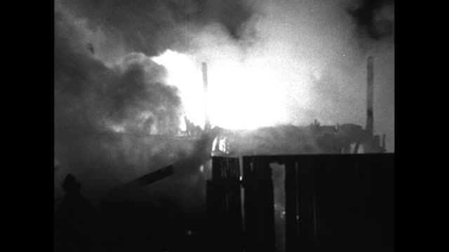 stockvideo's en b-roll-footage met three shots of lumber yard fire burning at night / stream of water from fire hose hitting fire / firemen using fire hoses to shoot streams of water... - fire hose