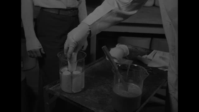 vídeos de stock e filmes b-roll de three shots of man in lab coat putting sleeve on other man's arm / man in lab coat puts rolls of plastic adhesive bandages in water / several shots... - elbow