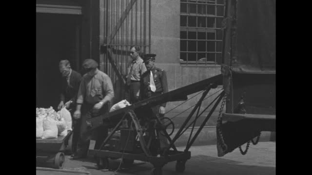 three shots of man loading cloth bags of coins from wagon onto conveyor belt that carries bags up into truck two guards standing and watching / four... - amerikanska mynt bildbanksvideor och videomaterial från bakom kulisserna