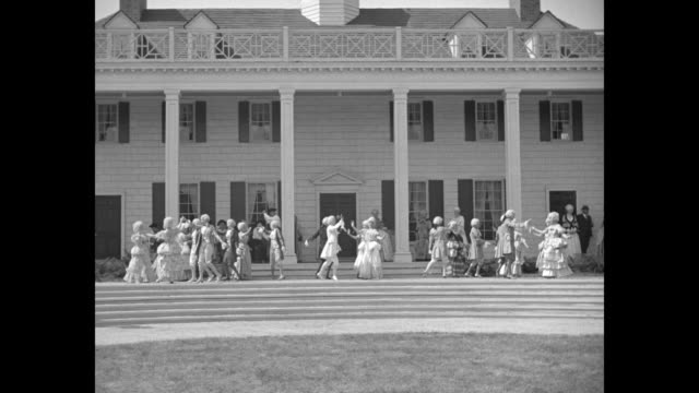 three shots of men and women in wigs and 18th century costumes dancing on facade of house / crowd of people walking across raised walkway / crowd... - chicago world's fair stock videos & royalty-free footage