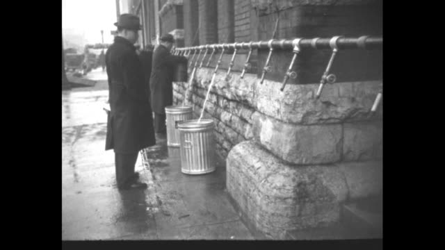 three shots of men cleaning mud off streets with push brooms / flooded waterworks building / men pumping water put of building / people getting water... - pontoon bridge stock videos and b-roll footage
