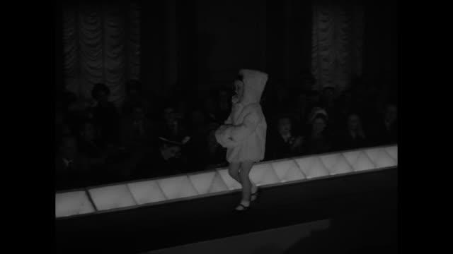 three shots of models walking on runway wearing fur coats / two shots of young girl on runway wearing fur coat with hood / men in crowd applauding /... - 毛皮のコート点の映像素材/bロール