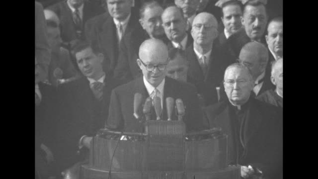 three shots of newly inaugurated pres. dwight eisenhower standing at podium on east portico of us capitol speaking, officials sitting behind him /... - 就任式点の映像素材/bロール
