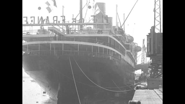 three shots of ocean liner ile de france sitting next to dock / two shots of stern of ship as it sits next to dock / shot from dock of side of ship /... - 旅客船点の映像素材/bロール