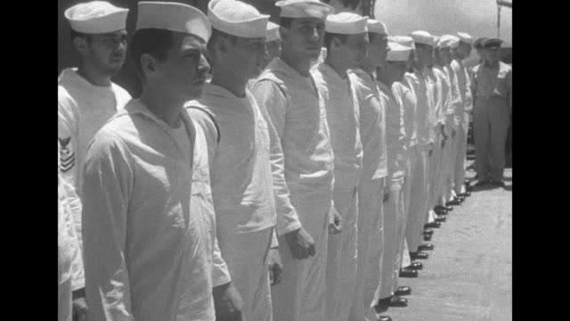 vídeos y material grabado en eventos de stock de three shots of officers and sailors standing in formation on deck of ship / sailors watching from ship anchored alongside / shot from behind sailors... - anclado