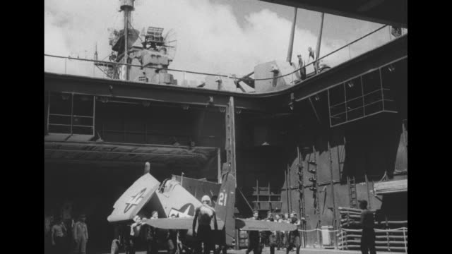 three shots of planes being lifted by crane off barge onto carrier as they are prepared for service in operation crossroads atomic bomb test in the... - bikini atoll stock videos & royalty-free footage