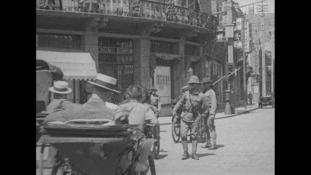 three shots of policemen of british shanghai municipal police patrolling street amid crowds of people / two shots of policemen standing next to... - 1920 stock videos & royalty-free footage