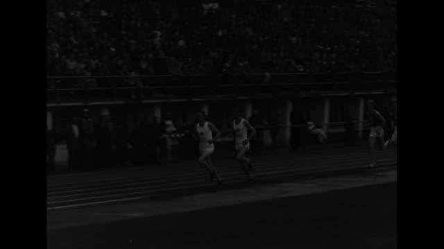 three shots of runners racing in olympic stadium / two shots of hungarian sandor iharos running in lead / iharos crosses finish line, tilt up to... - ハンガリー文化点の映像素材/bロール